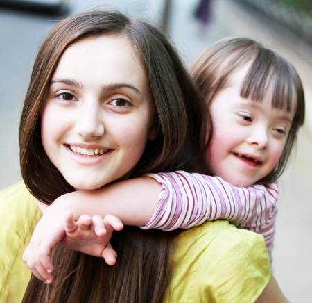 downs syndrome: Portrait of beautiful young girls in the park .