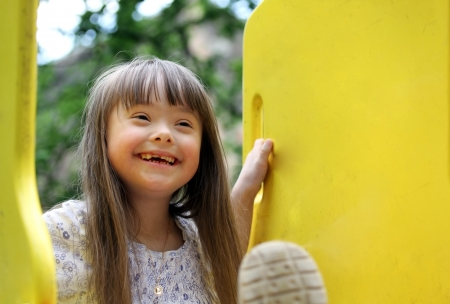 down's syndrome: Portrait of beautiful young girl on the playground