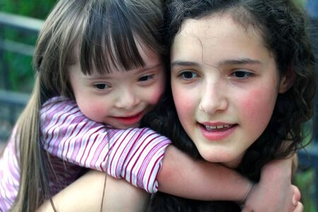 down's syndrome: Portrait of beautiful young girls in the park .