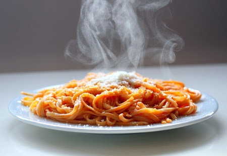 Italian spaghetti steaming with parmesan cheese.