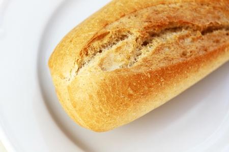 Baguette francés en un plato blanco Foto de archivo