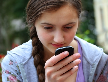 Girl with a mobile phone reads the message Stock Photo