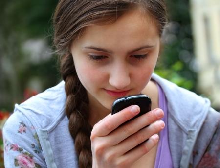 Mädchen mit einem Handy liest die Nachricht Standard-Bild