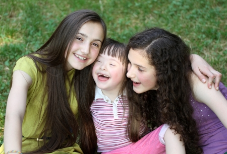 down syndrome: Happy little girl with sisters