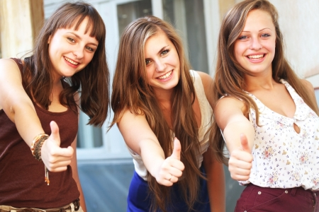 Beautiful student girls smiling and giving thumbs up Stock Photo