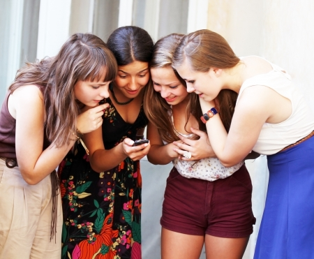 mobile communication: Beautiful student girls looking message on mobile phone Stock Photo