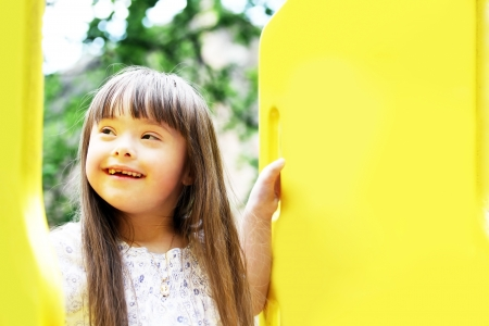eyes looking down: Portrait of beautiful young girl on the playground Stock Photo
