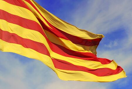 catalonian: Waving flag of the Catalunya (Catalonia) on background of the blue sky. Stock Photo