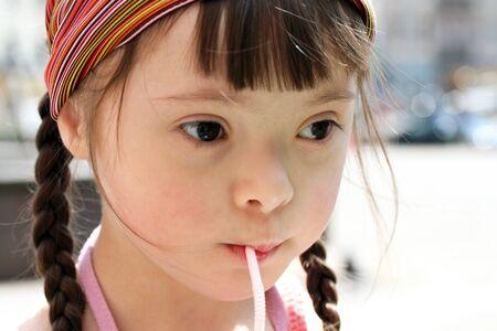 Portrait of little girl drinking water photo
