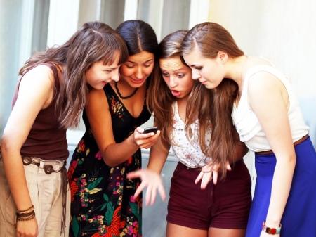 amigas conversando: Hermosas chicas estudiantes looking mensaje en el tel�fono m�vil Foto de archivo