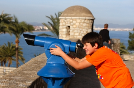 The boy looks through telescope . photo