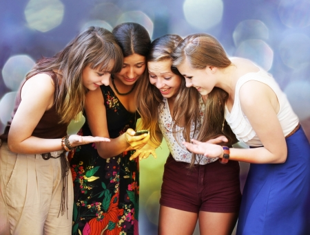 Beautiful student girls looking message on mobile phone Фото со стока
