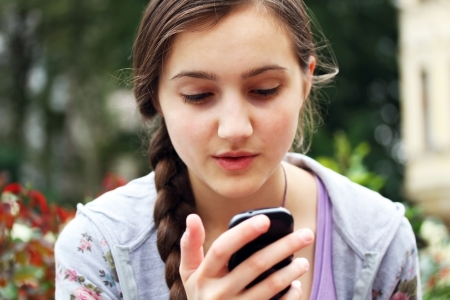 sms: Girl with a mobile phone reads the message Stock Photo