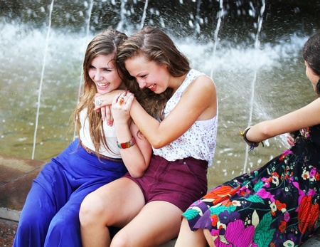 hot teen girl: Beautiful girls having fun with a fountain. Stock Photo