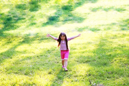 Happy little girl running in the park photo