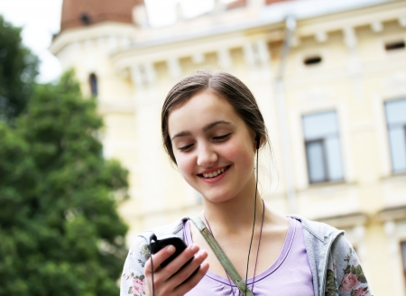 Girl listening music on mobile phone in the city photo