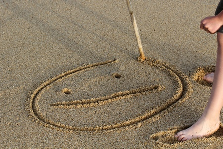 sand writing: A smiley face drawing on a sand. Stock Photo