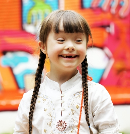 down syndrome: Portrait of beautiful young girl on the playground.