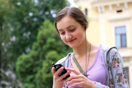 Girl listening music on mobile phone in the city