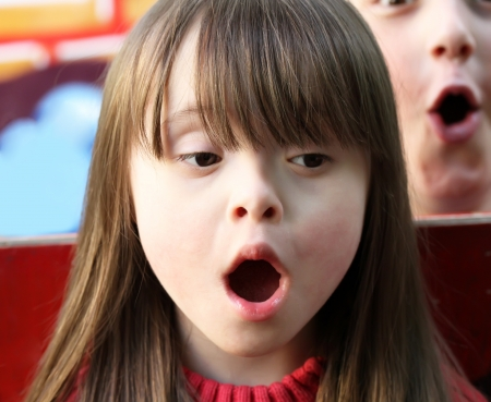 down's syndrome: Portrait of girl singing with a boy on the playground. Stock Photo