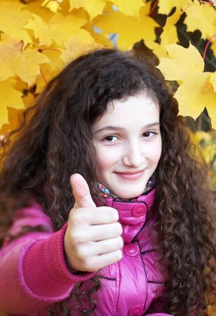 Portrait of beautiful young girl giving thumbs up on background of the yellow leaves photo