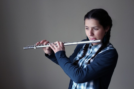 silver flute: Teenage girl plays the flute.