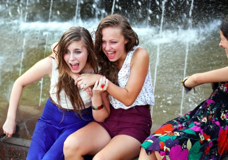jokes: Beautiful girls having fun with a fountain. Stock Photo