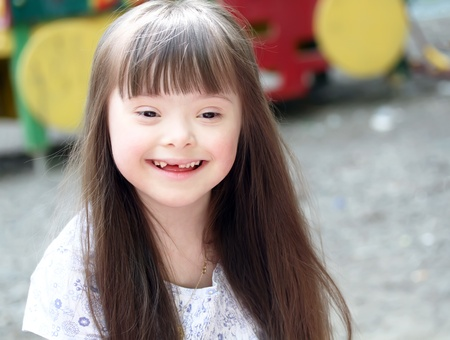downs syndrome: Portrait of beautiful young girl on the playground.