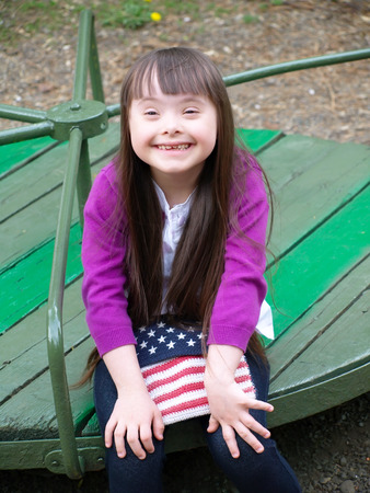 downs syndrome: Portrait of beautiful young girl on the playground Stock Photo