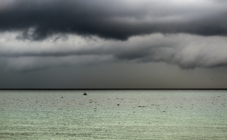 strong wind: Huge black storm clouds gather on the sea