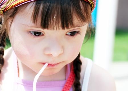 Portrait of little girl drinking juice photo