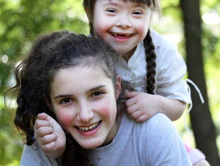 down's syndrome: Happy family moments - sisters have a fun. Stock Photo