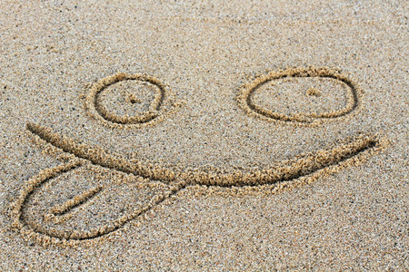 A smiley face drawing on a sand  photo