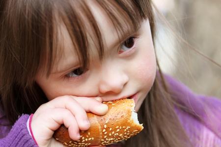 Portret van een mooi meisje dat het eten van stokbrood
