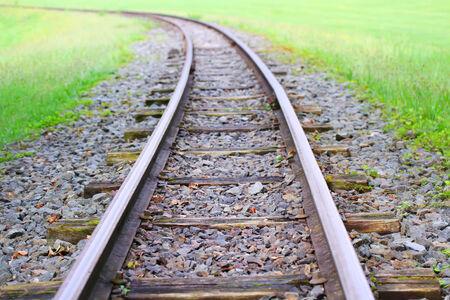Railway goes to horizon in green grass photo