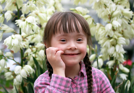 downs syndrome: Portrait of beautiful young girl on flowers background