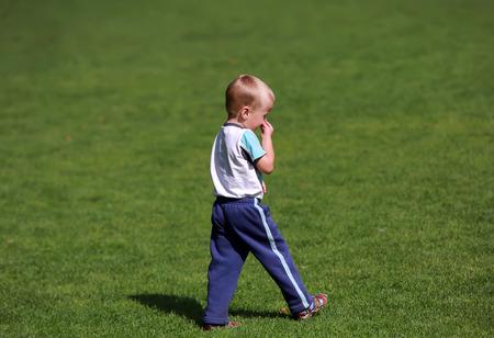 Boy walking on the park grass photo