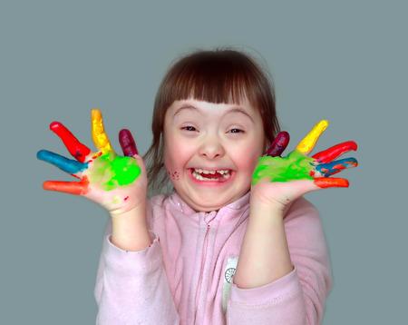 Schattig klein meisje met geschilderde handen. Geïsoleerd op een grijze achtergrond.