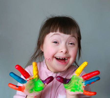 Cute little girl with painted hands. Isolated on grey background. Foto de archivo