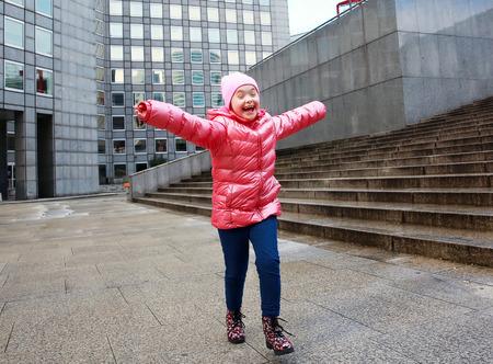 run down: Portrait of beautiful happy little girl in the city