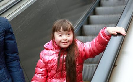 bajando escaleras: Retrato de la hermosa niña en las escaleras mecánicas