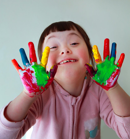 painted hands: Cute little girl with painted hands. Isolated on grey background. Stock Photo