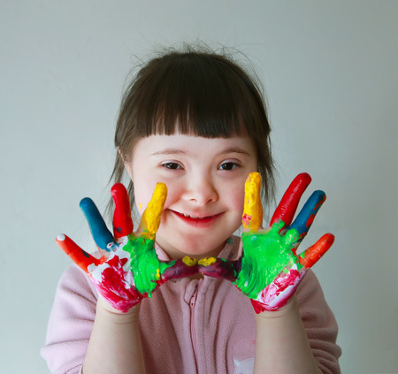 messy paint: Cute little girl with painted hands. Isolated on grey background. Stock Photo