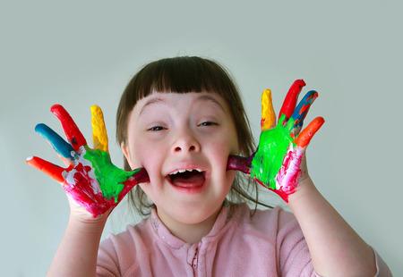 personas discapacitadas: Niña linda con las manos pintadas. Aislado en el fondo gris.