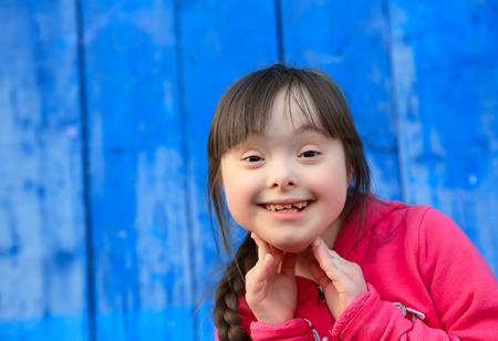 青い壁の背景に笑っている若い女の子 写真素材