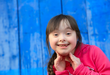 Young girl smiling on background of the blue wall 스톡 콘텐츠