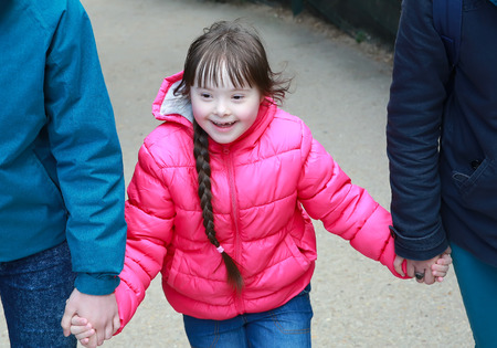 child hand: Girl holding arms of parents on a walk