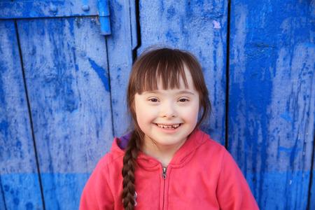 niños discapacitados: Chica joven que sonríe en el fondo de la pared azul. Foto de archivo