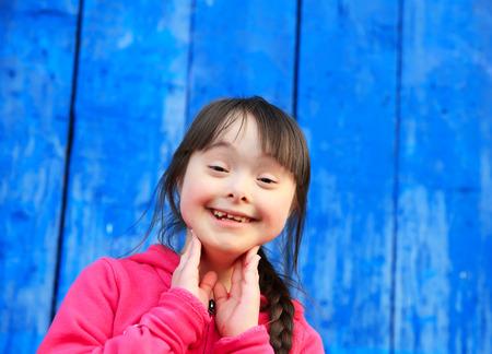 discapacidad: Chica joven que sonr�e en el fondo de la pared azul