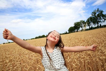Jong meisje hebben plezier in het tarweveld Stockfoto